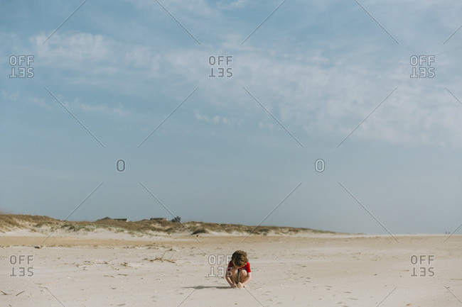 Boy crouching at beach against blue sky during sunny day