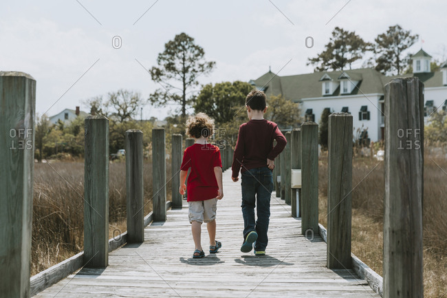 Rear view of brothers walking on boardwalk against clear sky during sunny day