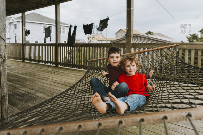 Portrait of cute brothers relaxing on hammock in balcony at tourist resort