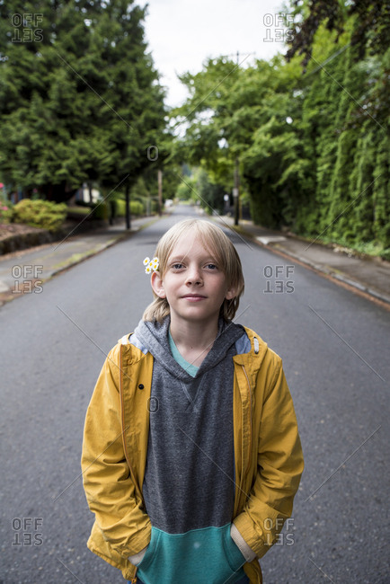 Portrait of boy with hands in pockets standing on road in park
