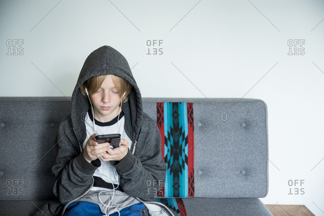 Boy in hooded jacket using mobile phone while sitting on sofa against wall at home