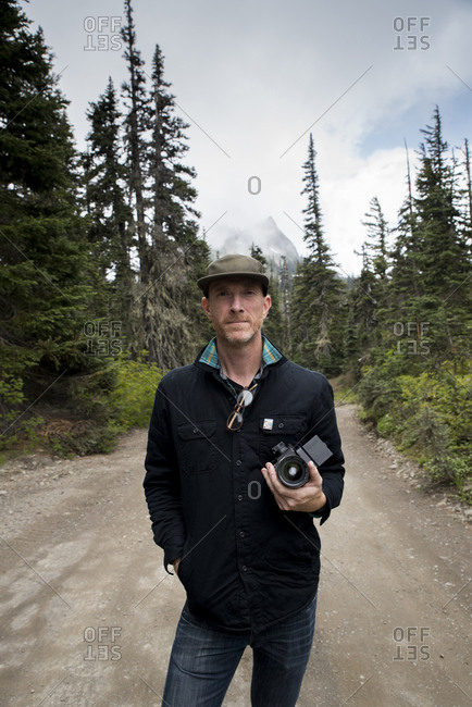 Portrait of man holding camera while standing on road against cloudy sky in Olympic National Park