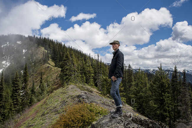 Side view of man looking away while standing on mountain against cloudy sky in Olympic National Park