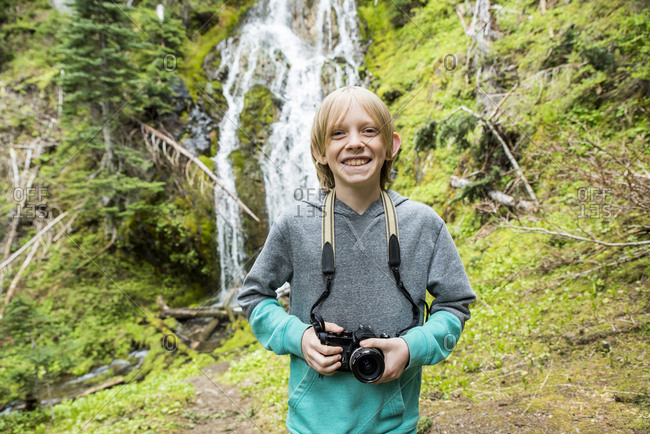 Portrait of smiling boy holding camera while standing against waterfall in Olympic National Park