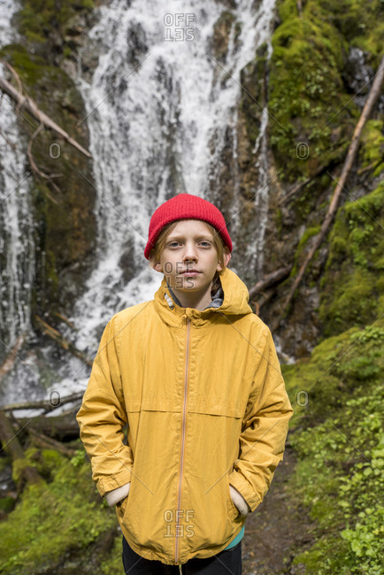Portrait of boy with hands in pockets standing against waterfall in Olympic National Park