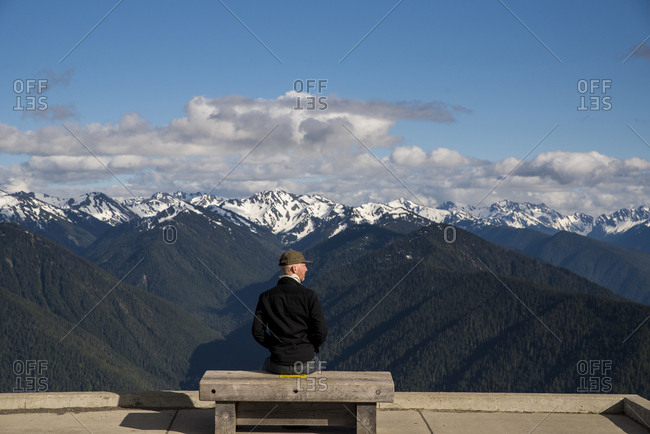 Rear view of man looking at snowcapped mountains while sitting on bench at Olympic National Park