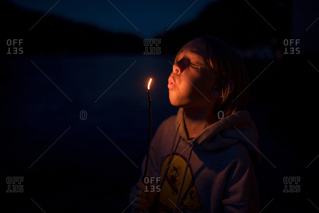 Boy blowing burning stick while standing in Olympic National Park at night