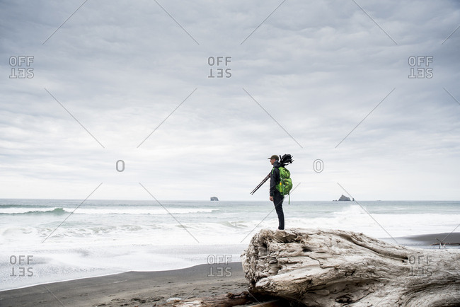 Side view of male hiker standing on log at beach against cloudy sky in Olympic National Park