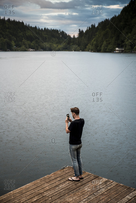 Side view of man photographing with mobile phone while standing on pier over lake in Olympic National Park
