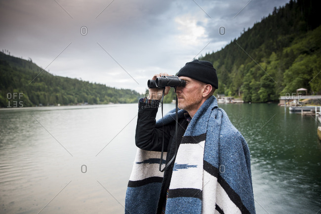Side view of man looking through binoculars while standing by lake against cloudy sky in Olympic National Park