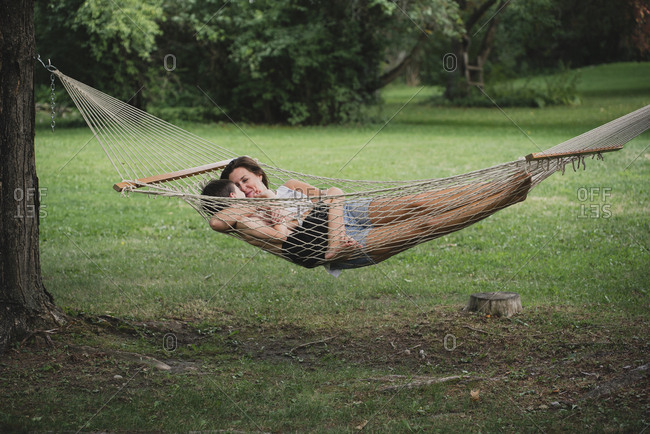 Mother with son relaxing on hammock in forest