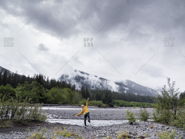Boy with arms outstretched balancing on field against cloudy sky in Olympic National Park
