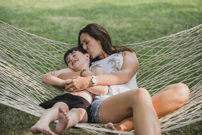 High angle view of mother kissing son while relaxing on hammock in forest