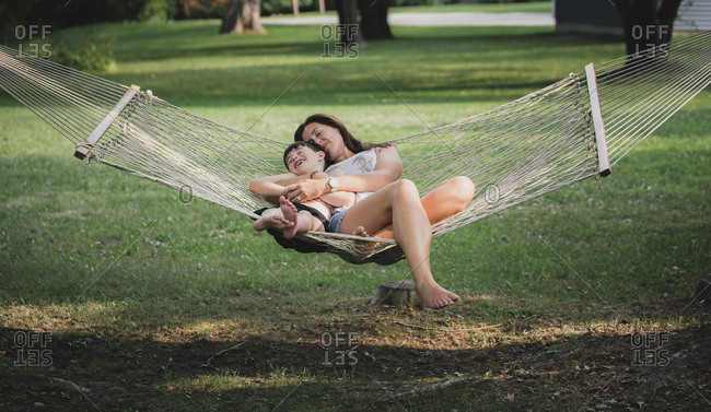 High angle view of mother with son sleeping on hammock in forest