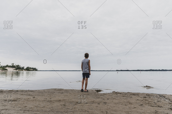 Rear view of boy standing at beach against cloudy sky