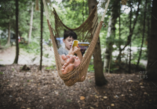 Full length of boy reading book while relaxing on hammock in forest