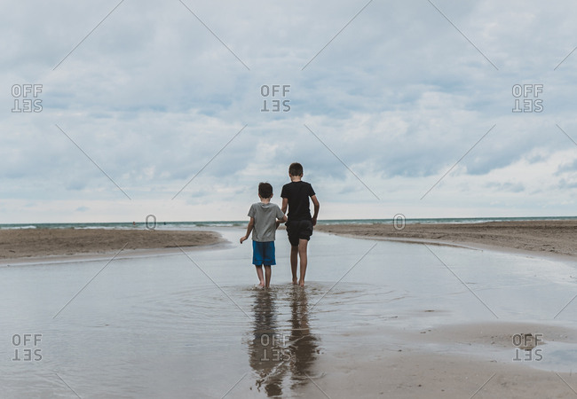 Rear view of brothers walking at beach against cloudy sky