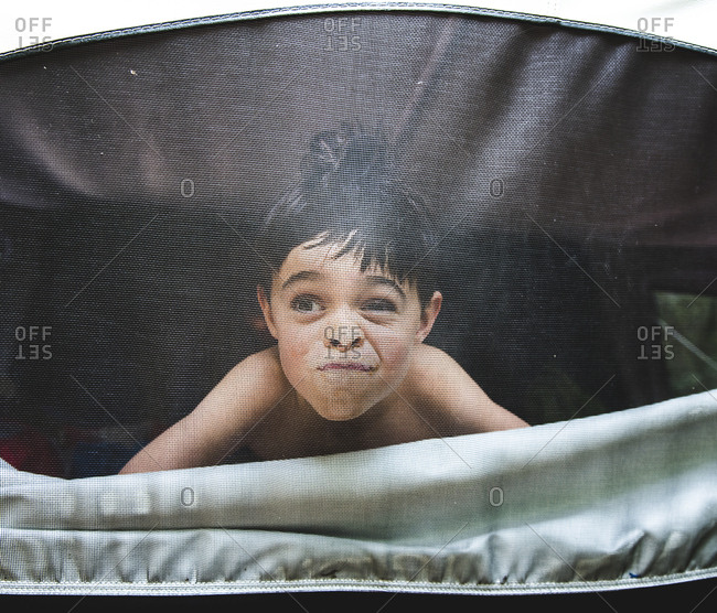 Boy making face while looking through tent