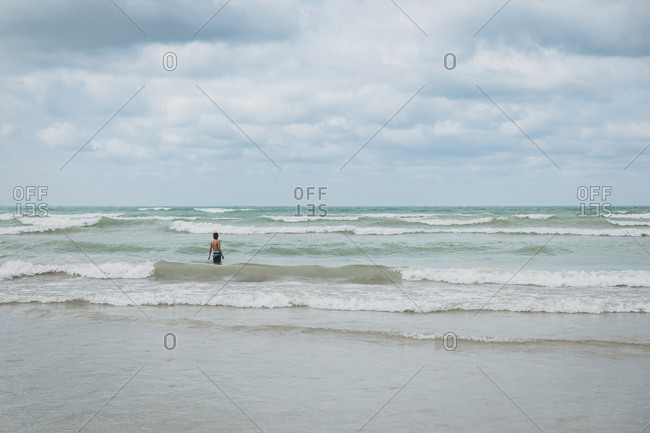 Rear view of shirtless boy standing in sea against cloudy sky