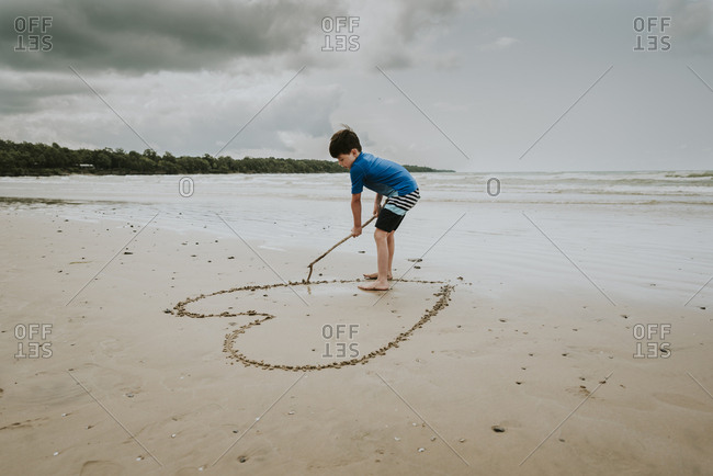 Boy making heart shape on sand at beach against cloudy sky