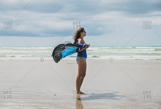 Side view of woman in swimwear holding sarong while standing at beach against cloudy sky during sunny day