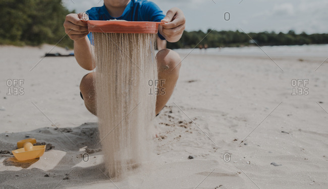 Low section of boy sieving sand while crouching at beach