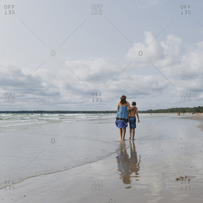 Rear view of mother with shirtless son walking at beach against cloudy sky