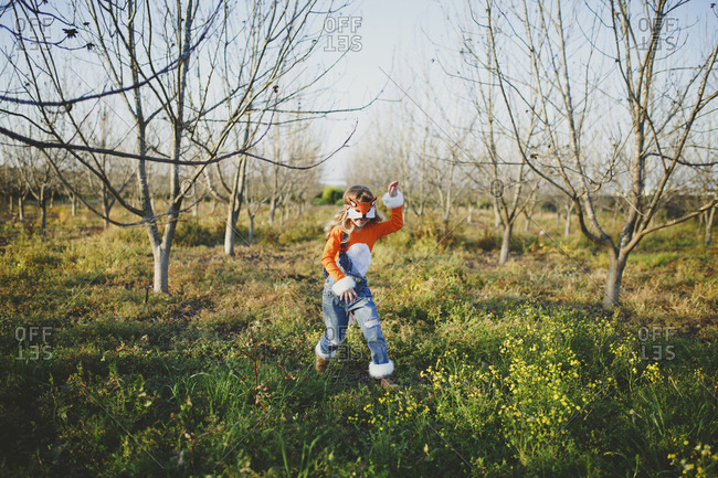 Girl in fox costume running on grassy field against sky during Halloween at park