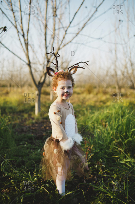 Portrait of cute girl in deer costume standing on grassy field against sky at park during Halloween