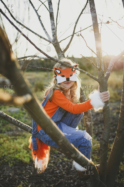 Portrait of girl in fox costume sitting on bare tree against sky during Halloween at sunset