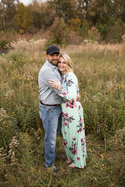 Portrait of smiling couple embracing while standing on grassy field against trees in forest