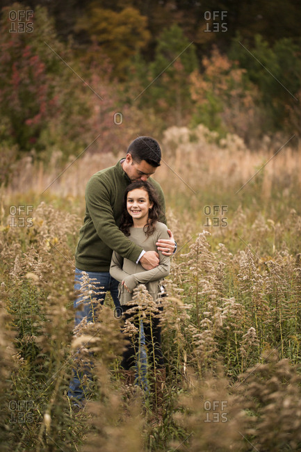 Father kissing on daughter's head while standing amidst plants in forest