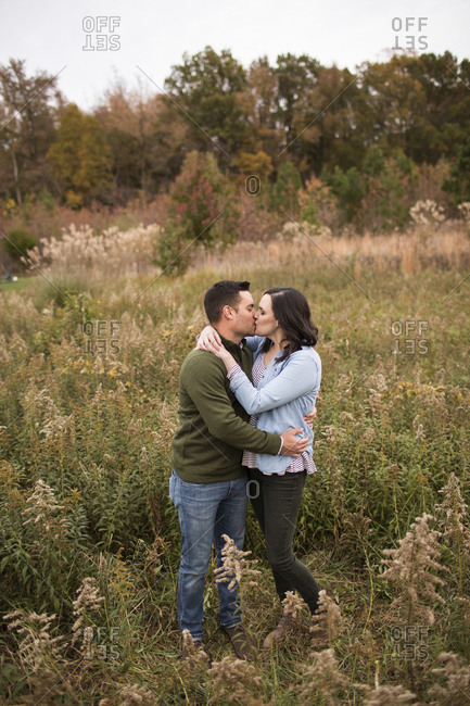 Couple kissing while standing on grassy field in forest