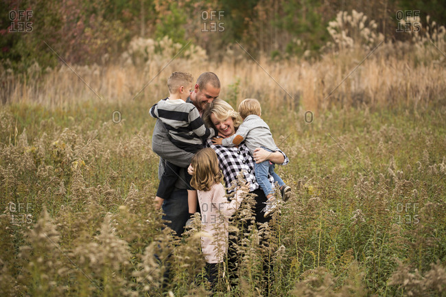 Happy parents embracing children while standing amidst plants in forest