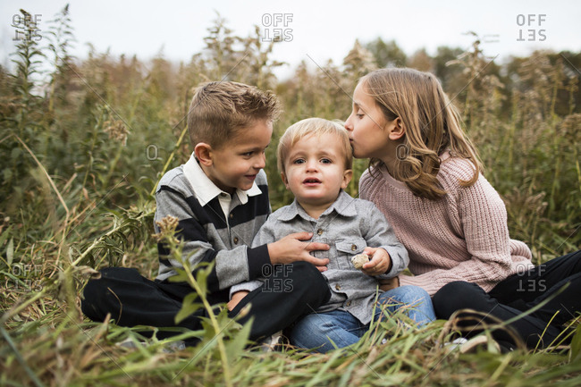 Portrait of cute baby boy with siblings sitting on grassy field in forest