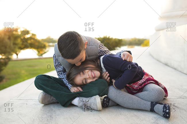 Portrait of happy sister lying on brother's lap while sitting against clear sky at park during sunset