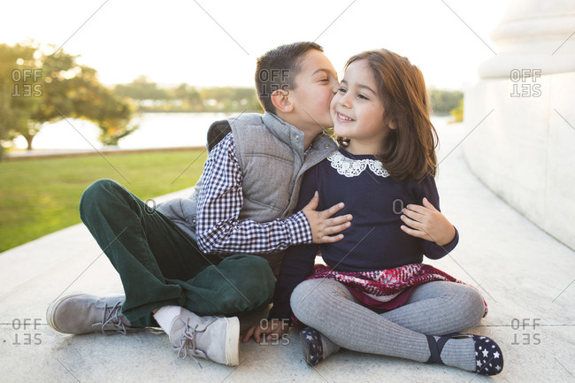 Happy brother kissing sister while sitting on retaining wall against clear sky at park during sunset