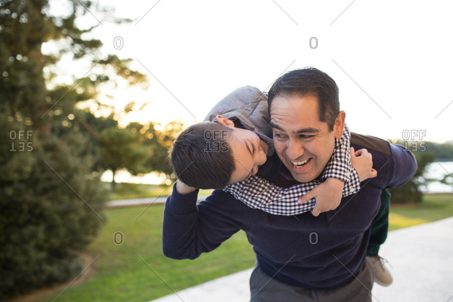 Happy father carrying son while standing against clear sky at park during sunset