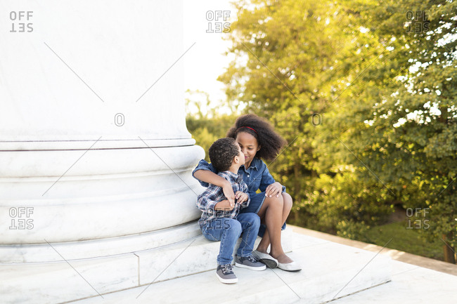 Siblings kissing while sitting on steps against trees at park