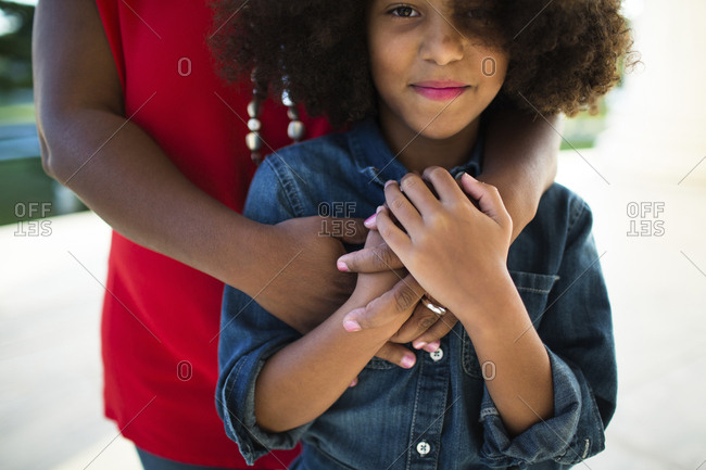 Midsection of mother with smiling daughter standing outdoors
