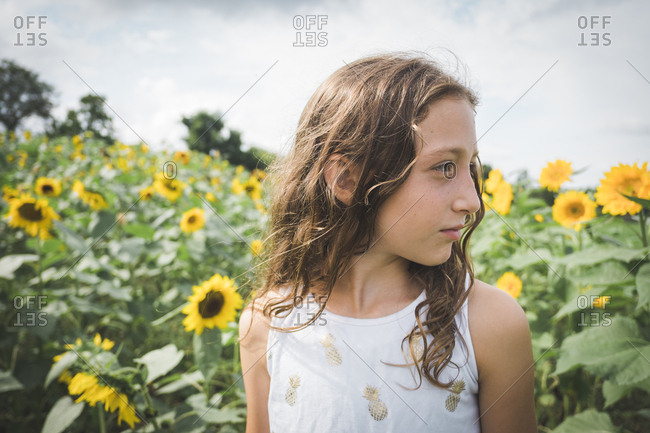 Thoughtful girl looking away while standing amidst plants against cloudy sky
