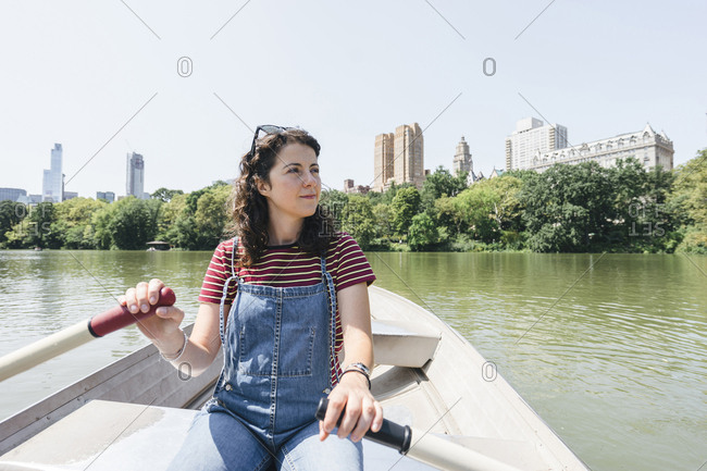 Woman looking away while rowing boat on lake against clear sky at Central Park