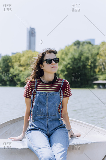 Woman wearing sunglasses sitting in boat on lake against clear sky at Central Park