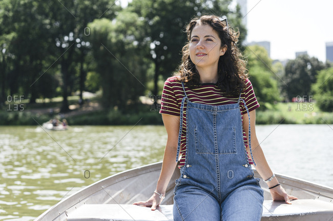 Woman looking away while sitting in boat on lake against trees at Central Park
