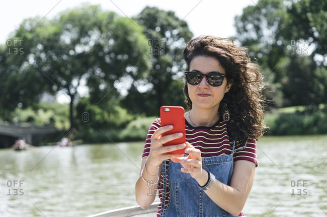 Woman wearing sunglasses taking selfie while sitting in boat on lake against trees at Central Park