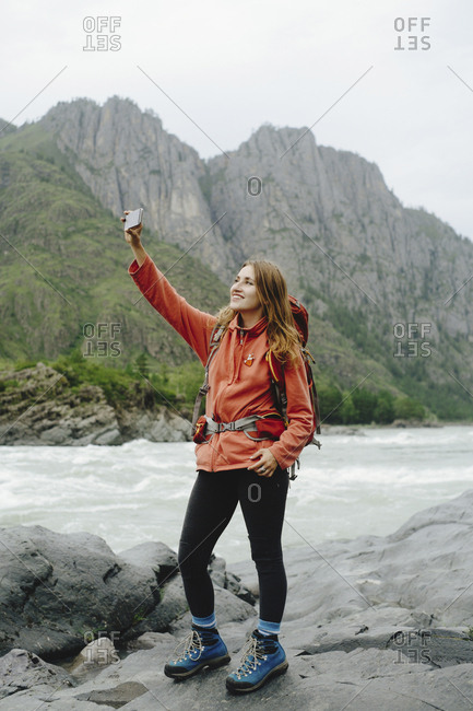 Smiling female hiker photographing with mobile phone while standing on rocks at riverbank against mountain