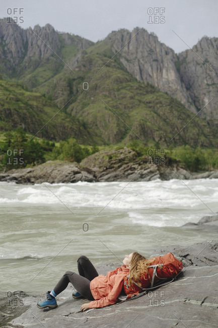 Female hiker reclining on backpack at riverbank against mountain