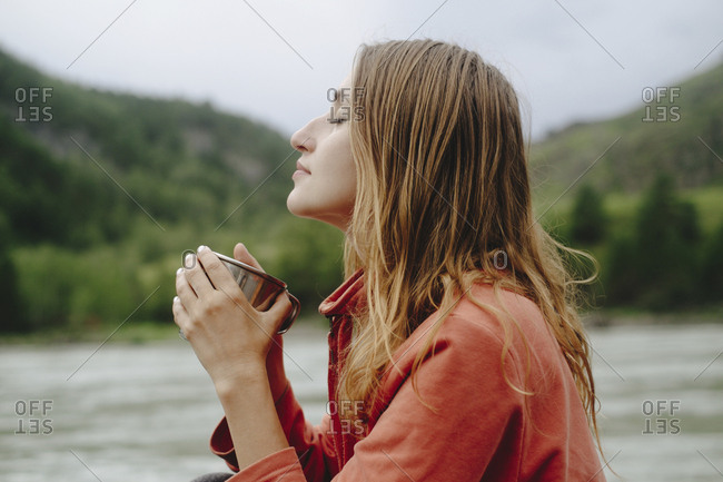 Side view of female hiker with eyes closed having tea while sitting at riverbank against sky