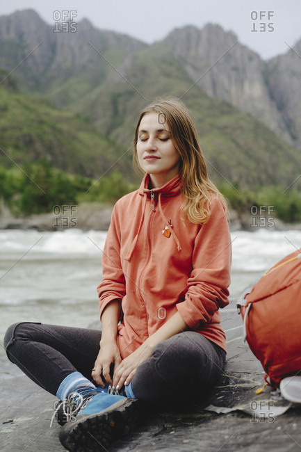Female hiker with eyes closed relaxing on rocks at riverbank against mountain
