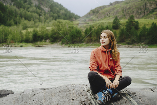 Thoughtful female hiker relaxing on rock at riverbank against mountain